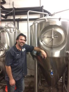 Francis Booth takes a rare photo opportunity with a beautiful stainless steel 10 BBL conical fermenter.